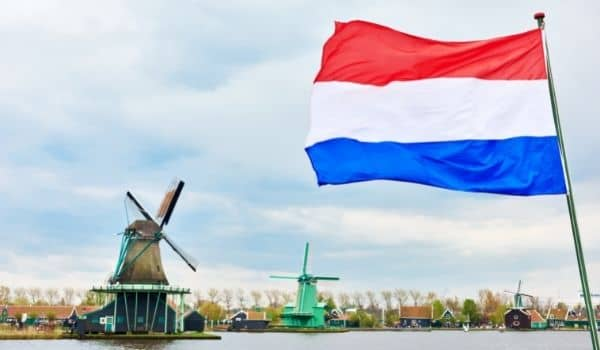 Why ISn;t the Dutch Flag Orange? A Picture of a red, white and blue ducth flag with a windmill in the background